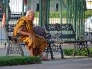 älterer Mönch nimmt sich seine Pause auf einer Parkbank in Bangkok